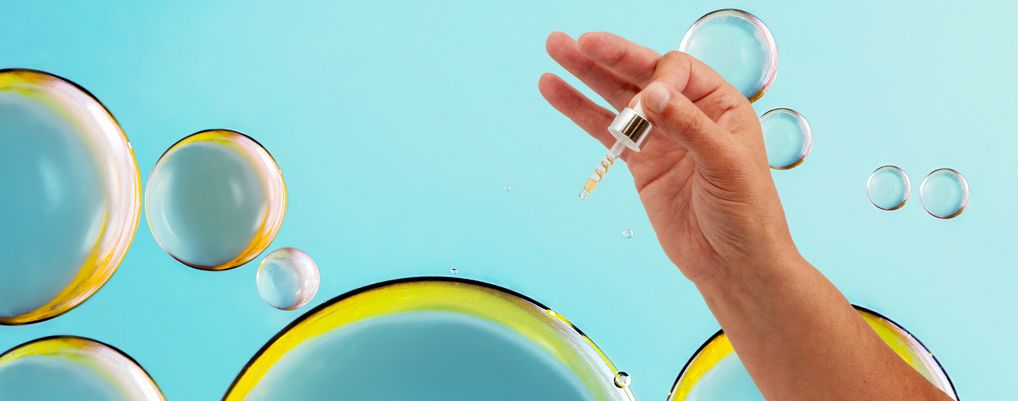 A hand holding a dropper on bubble background