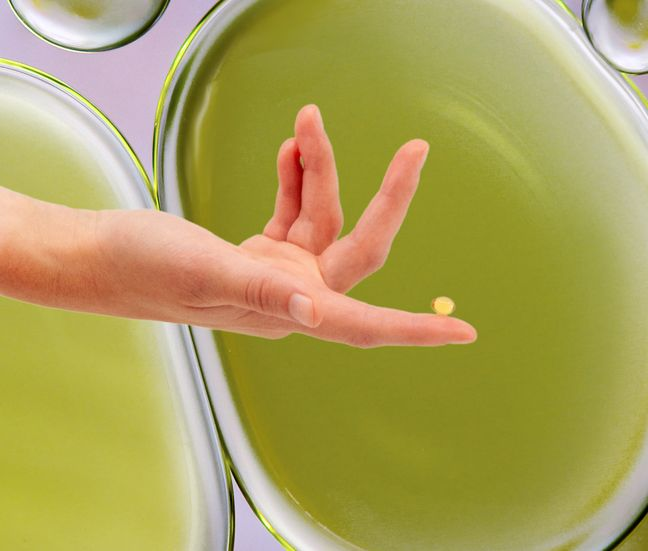 A hand holding a capsule on bubble background