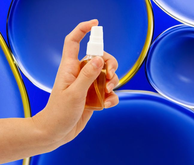 A hand holding an oral spray on bubble background